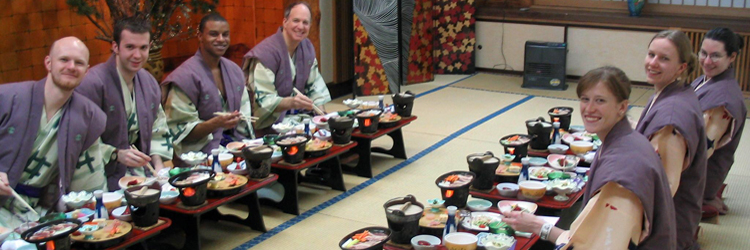 Students wearing traditional Japanese clothing (Yukata) seated to eat dinner.