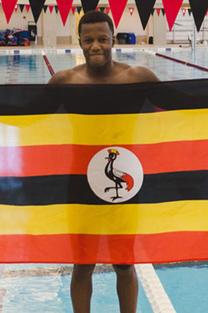 Joshua Tibatemwa '19 in Grinnell's natatorium holding Ugandan flag