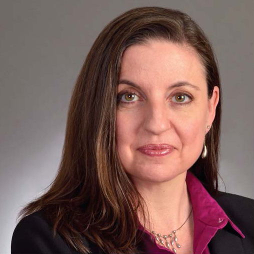 Light skinned woman with brown hair wearing a purple shirt under a black blazer against a gray background