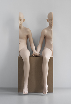 Sculpture that appears to be a person in two halves, swapped left to right and holding hands