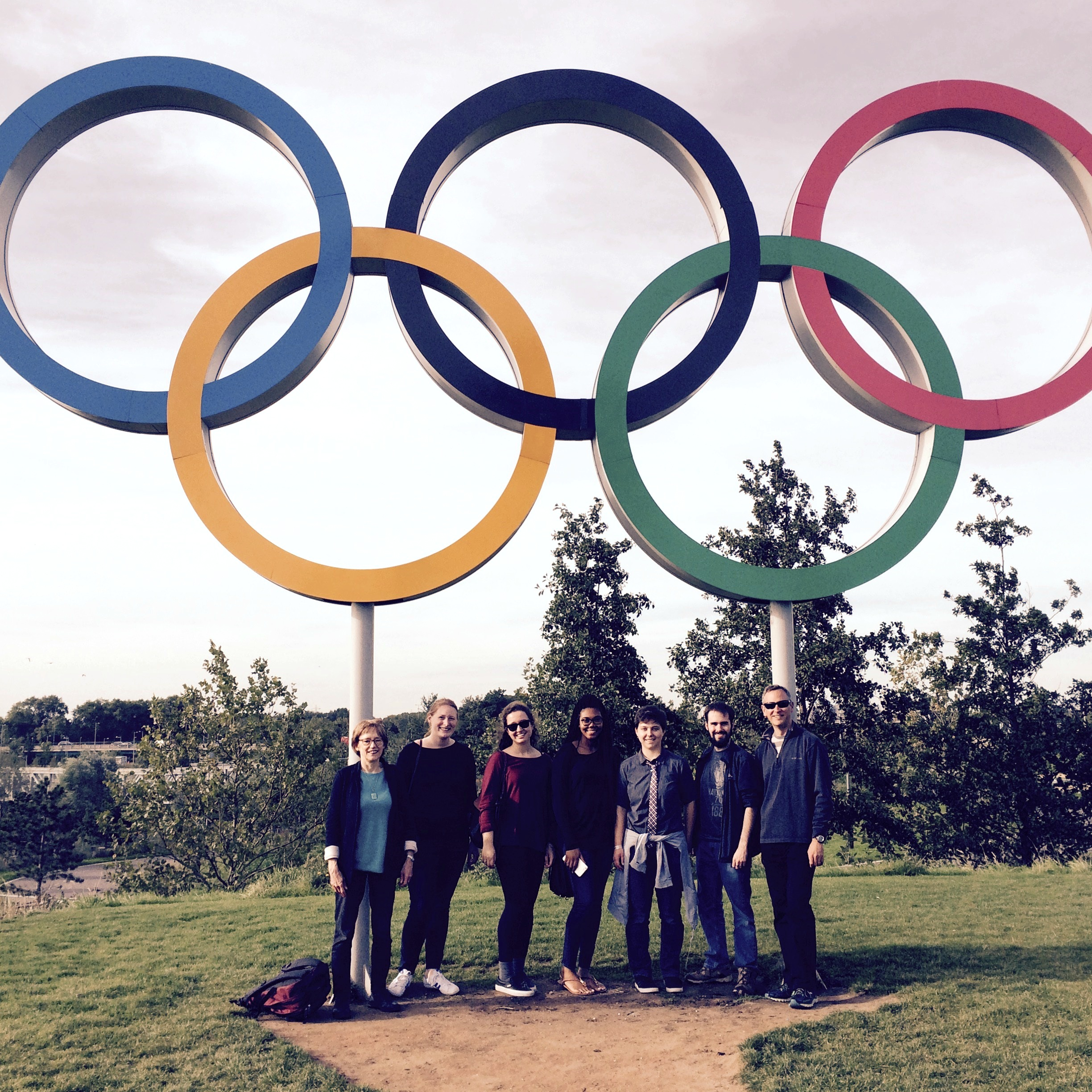 Group of students standing under Olympic rings