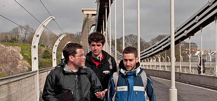 Three men crossing a bridge