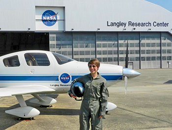 Larson in flight suit in front of plane