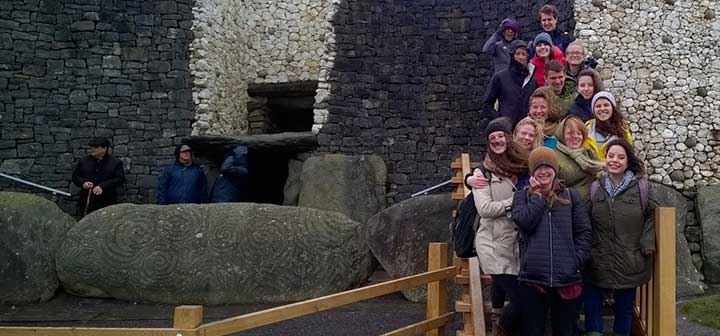 Students and professor pose on steps near Newgrange near large rocks decorated with the famous tri-spiral
