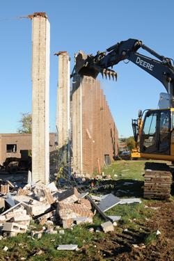 Clawed diesel shovel pulls brick away from concrete block pillars