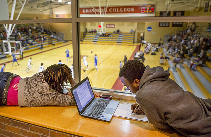 Students study and watch game through window overlooking Darby Gym