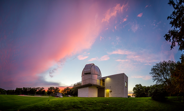Pink clouds over green field are reflected in metal-clad observatory