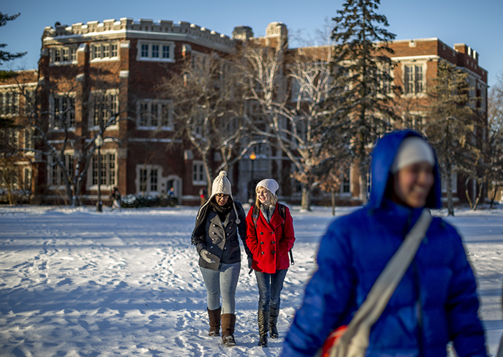 Students walking across snow-covered lawn with ARH in the background