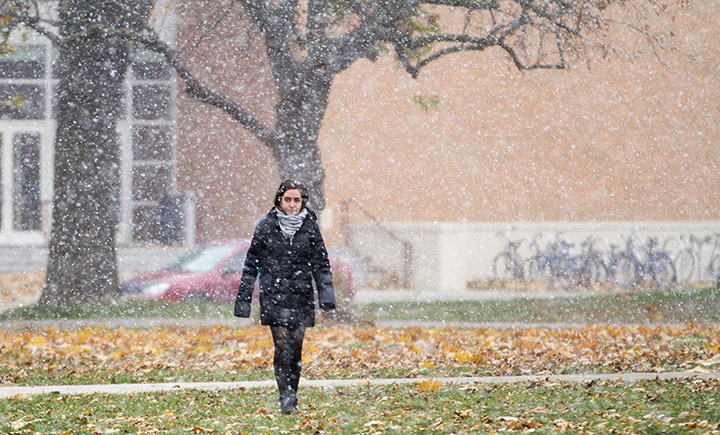 Student walking on the grass in snowfall