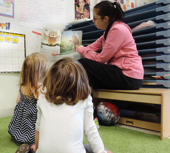 Teacher's aide holding book open and reading to two young children.