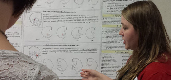 A student explains her neuroscience research project to a conference participant.