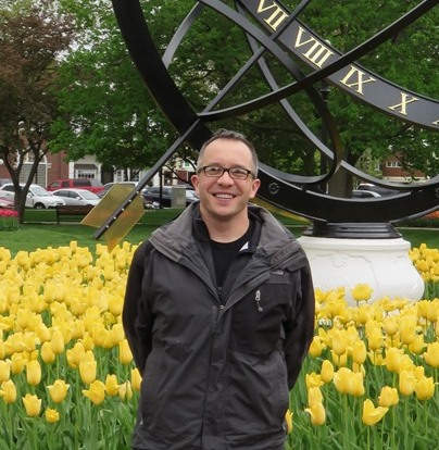 Nathaniel Rosi '99 in front of a large sundial and yellow tulips in Pella, IA.