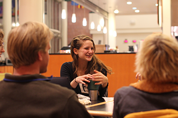 Three students talking together in a committee