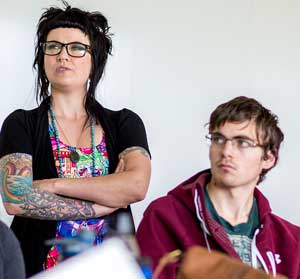 Jennifer Snook and a student concentrate on an issue in class