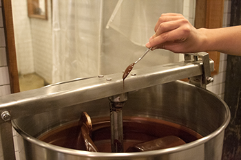 Stirring a vat of chocolate with a large spoon