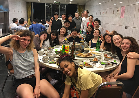 Large group of students, faculty, and collaborating actors sit around a table at a restaurant in Taiwan