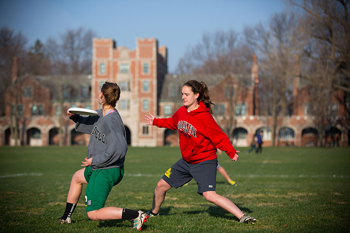 Two students play ultimate frisbee in front of north campus residence halls