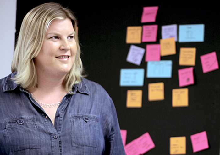 Jocelyn Wyatt '99 standing in front of work board covered in post-it notes