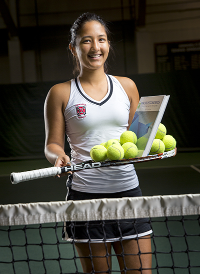 Anushka Joshi '18 holds tennis racket with book, balls balanced on top