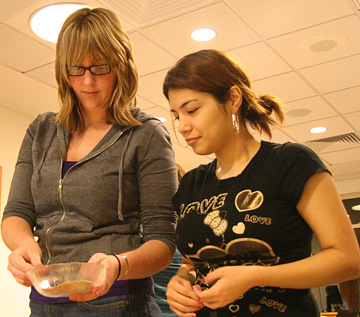 One woman watches while another shows her the bowl with yeast in it.