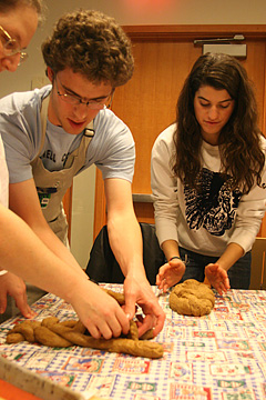 Two people braid dough while a third pats a completed loaf into shape.