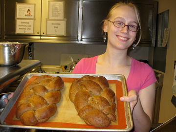 Woman holding a sheet pan with two cooked loaves of bread.