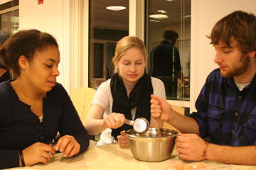 Man stirs contents of a bowl while woman adds something from a measuring cup. Third person watches.