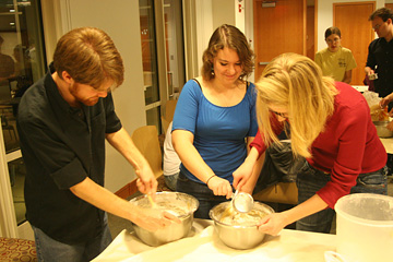 Three people working over two bowls of dough.
