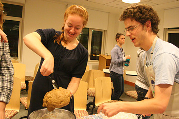 Woman cutting a ball of dough with kitchen shears. Man stands ready beside her.