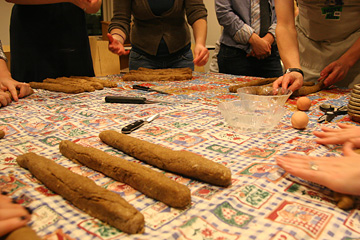 People surrounding a table with several strips of dough and a few balls ready for rolling.