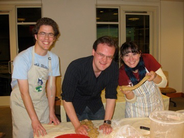 Three people ham for the camera in aprons next to a flour-covered table.