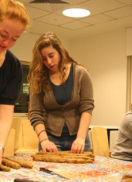 Women line up rolls of dough to braid.