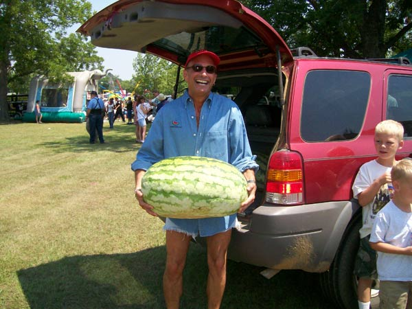 Chef Harry carrying a huge watermelon at the back of a vehicle