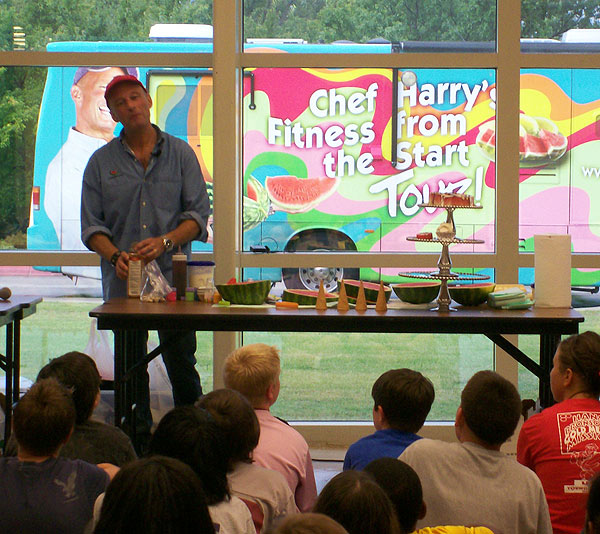 Harry in front of a table with ingredients, class of students watch him, and the bus is visible through the windows