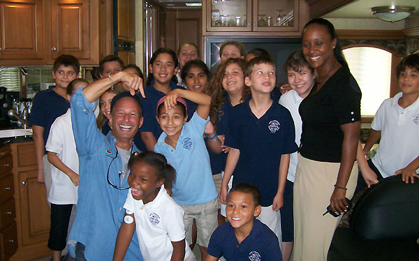 Harry poses with the group of kids in a kitchen. Harry and a kid both point at a laughing girl in front of them