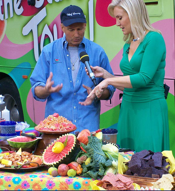 Harry and reporter in front of a table laden with food in front of the bus