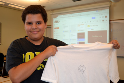 Student holds up white t-shirt stitched with offset concentric circles and a 'tail'