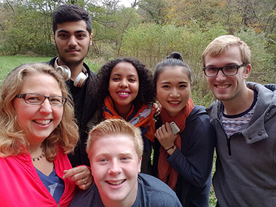 An FIS host poses with her international students