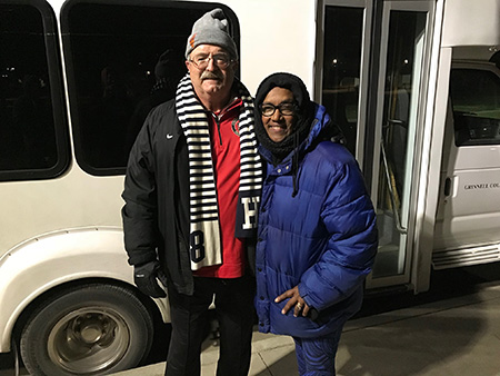 Will Freeman and Kesho Scott stand in front of a bus