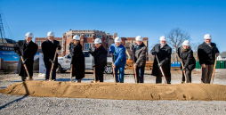 Members of the board of trustees, administrators, and city officials hold shovels on the site of the new construction