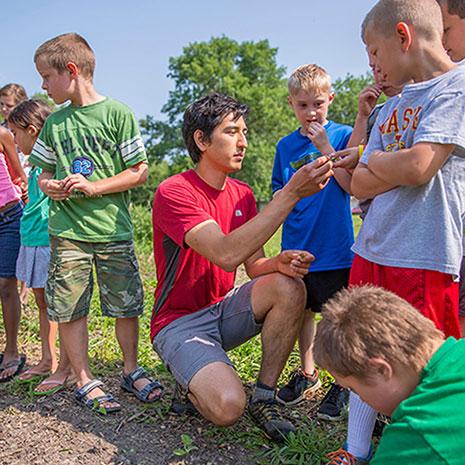 student works with children in community garden