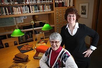 Catherine Rod (right) Cheryl Neubert at lit table with bookshelves and card catalog in back