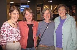 Four women arm-in-arm at an airport