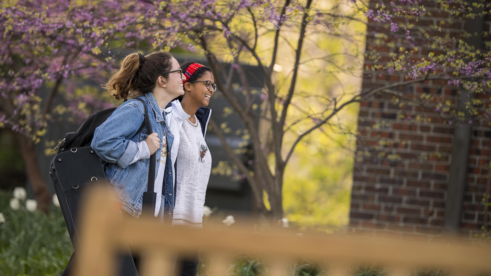two students walk in front of Steiner Hall