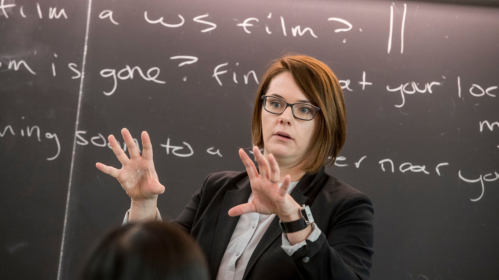 Professor gestures at front of class