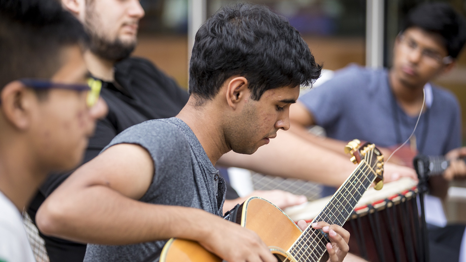students play guitars and drums outdoors