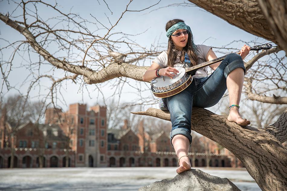 Cherylyn Geers '14 playing banjo in tree