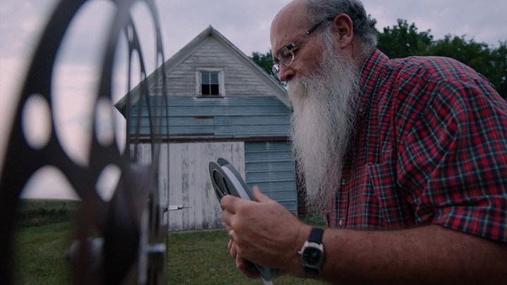 Bearded man inspects film reel outside on a farm
