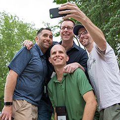 Four reunion attendees pose for a seflie photo