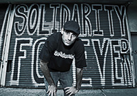 "Samuel Sellers '00 poses in front of a corrugated steel door with graffiti saying ""Solidarity Forever"""